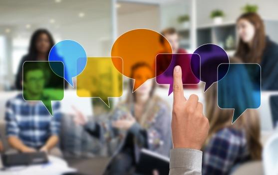Personas hablando de fondo con indicadores de colores indicando diferentes idiomas