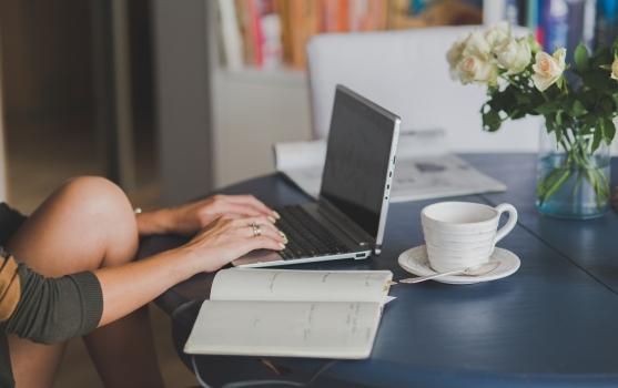 persona con computadora portátil dentro de un ambiente agradable con plantas, anotador y taza de café