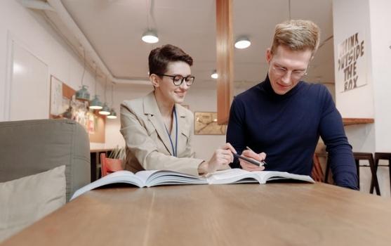 ein Mann und eine Frau, die zusammen mit einem Buch Englisch lernen