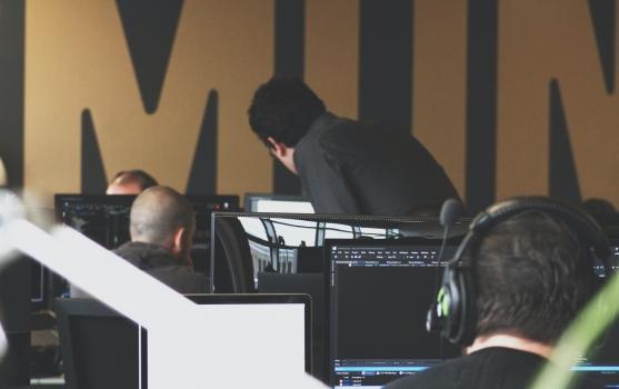 profesionales trabajando junto a computadores y micrófonos